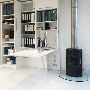 Diseño de estudio actual, pequeño, con paredes blancas, suelo de madera clara, estufa de leña y escritorio empotrado