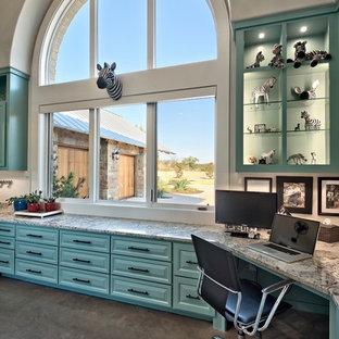 オースティンの広いトランジショナルスタイルのおしゃれなアトリエ・スタジオ (青い壁、コンクリートの床、造り付け机) の写真