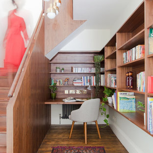 Inspiration for a midcentury study in London with white walls, medium hardwood flooring, a built-in desk and brown floors.