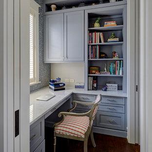 Modelo de despacho tradicional, pequeño, con paredes azules, suelo de madera oscura, escritorio empotrado y suelo marrón