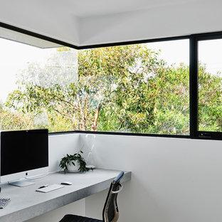 Idée de décoration pour un bureau minimaliste de taille moyenne et de type studio avec un mur blanc, un sol en bois clair, un bureau intégré et un sol marron.