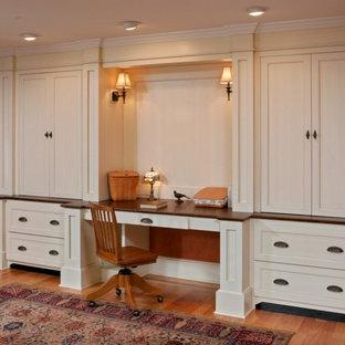 Ejemplo de despacho tradicional, de tamaño medio, con parades naranjas, suelo de madera clara y escritorio empotrado