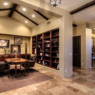 デンバーの巨大な地中海スタイルのおしゃれなホームオフィス・仕事部屋 (ライブラリー、ベージュの壁、トラバーチンの床、自立型机、ベージュの床) の写真