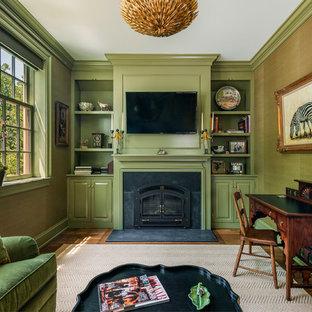 Inspiration för mellanstora klassiska hemmabibliotek, med gröna väggar, mellanmörkt trägolv, en standard öppen spis, ett fristående skrivbord och en spiselkrans i sten