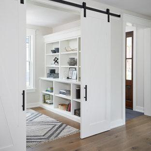 Kleines Country Arbeitszimmer mit weißer Wandfarbe und braunem Holzboden in Grand Rapids