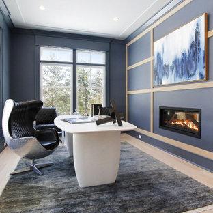 ニューヨークの広いコンテンポラリースタイルのおしゃれなホームオフィス・書斎 (青い壁、淡色無垢フローリング、吊り下げ式暖炉、自立型机、ベージュの床、パネル壁) の写真