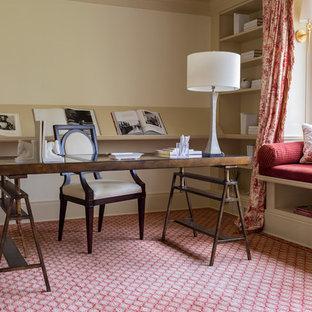 Inspiration för mellanstora klassiska hemmabibliotek, med beige väggar, heltäckningsmatta, ett fristående skrivbord och rött golv