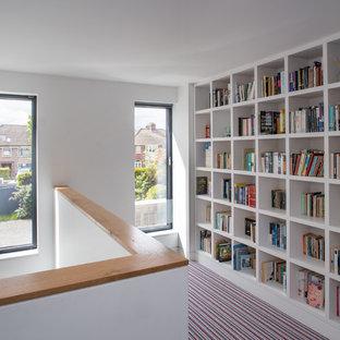 ダブリンの中くらいのコンテンポラリースタイルのおしゃれなホームオフィス・書斎 (ライブラリー、白い壁、カーペット敷き、自立型机、マルチカラーの床) の写真