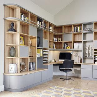 Idee per un ufficio minimal con pareti bianche, pavimento con piastrelle in ceramica, scrivania incassata e pavimento beige