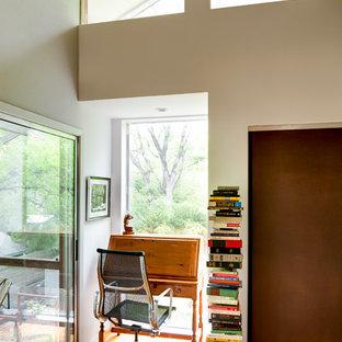 Inredning av ett industriellt arbetsrum, med beige väggar, plywoodgolv och ett fristående skrivbord