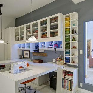 Inredning av ett klassiskt mellanstort hobbyrum, med grå väggar, klinkergolv i porslin, ett inbyggt skrivbord och vitt golv