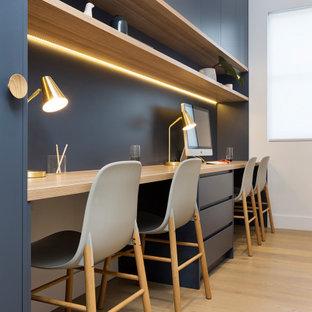 Idéer för att renovera ett mellanstort funkis hemmabibliotek, med vita väggar, ljust trägolv, ett inbyggt skrivbord och gult golv