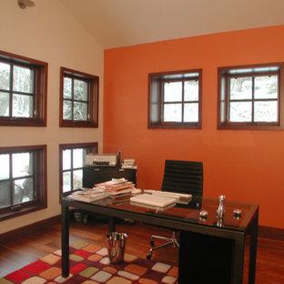 デンバーの中サイズのモダンスタイルのおしゃれなホームオフィス・書斎 (オレンジの壁、無垢フローリング、暖炉なし、自立型机、ベージュの床) の写真