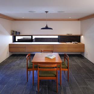 Idéer för ett stort modernt hemmabibliotek, med vita väggar, skiffergolv, ett inbyggt skrivbord och grått golv