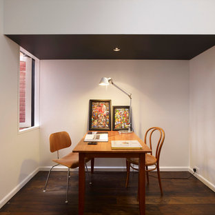 Home office - modern freestanding desk dark wood floor home office idea in Sydney with white walls and no fireplace
