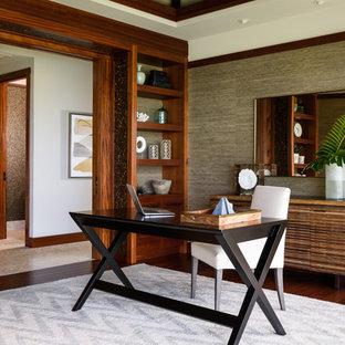 Cette photo montre un grand bureau exotique avec un sol en bois foncé, un bureau indépendant et un mur beige.