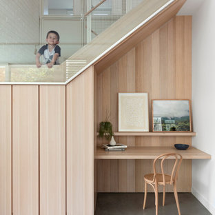 This is an example of a small scandinavian study room in Melbourne with white walls, concrete floors, no fireplace, a built-in desk and grey floor.