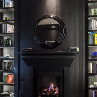 Inspiration för mellanstora klassiska hemmabibliotek, med bruna väggar, mörkt trägolv, en standard öppen spis, en spiselkrans i sten och ett fristående skrivbord
