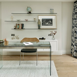 This is an example of a large classic home office and library in London with grey walls, light hardwood flooring, no fireplace, a freestanding desk and beige floors.