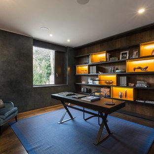 ロンドンの中くらいのトランジショナルスタイルのおしゃれなホームオフィス・書斎 (濃色無垢フローリング、自立型机、茶色い床、黒い壁) の写真