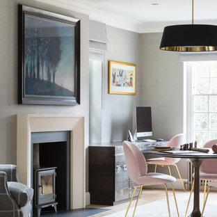 ロンドンのトランジショナルスタイルのおしゃれな書斎 (グレーの壁、薪ストーブ、造り付け机、茶色い床、淡色無垢フローリング) の写真