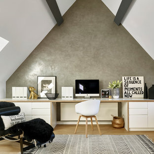 Design ideas for a contemporary study in London with grey walls, light hardwood flooring and a built-in desk.