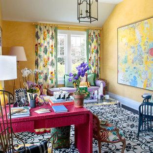 Exempel på ett stort eklektiskt hemmabibliotek, med gula väggar, mörkt trägolv, ett fristående skrivbord och flerfärgat golv