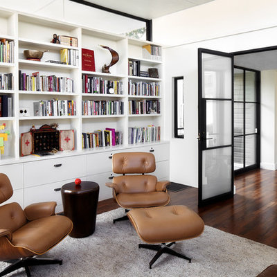 Example of a mid-sized trendy freestanding desk dark wood floor and brown floor study room design in Austin with white walls and no fireplace