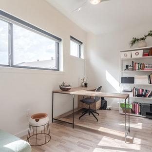На фото: маленькое рабочее место в скандинавском стиле с белыми стенами, светлым паркетным полом, отдельно стоящим рабочим столом и бежевым полом без камина с