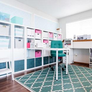 Modelo de sala de manualidades tradicional renovada, pequeña, con paredes blancas, suelo laminado y escritorio empotrado