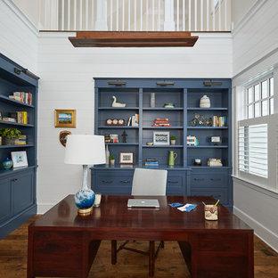 Foto på ett stort maritimt hemmabibliotek, med vita väggar, mellanmörkt trägolv, ett inbyggt skrivbord och brunt golv