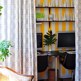 Eklektisk inredning av ett arbetsrum, med flerfärgade väggar och mellanmörkt trägolv