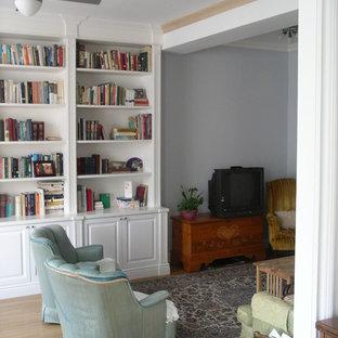 ニューヨークの中くらいのトランジショナルスタイルのおしゃれなホームオフィス・書斎 (ライブラリー、グレーの壁、淡色無垢フローリング、標準型暖炉、漆喰の暖炉まわり) の写真