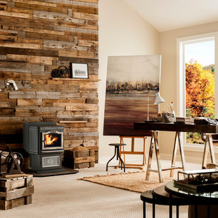 This is an example of a medium sized rustic study in New York with beige walls, carpet, a wood burning stove, a metal fireplace surround, a built-in desk and beige floors.