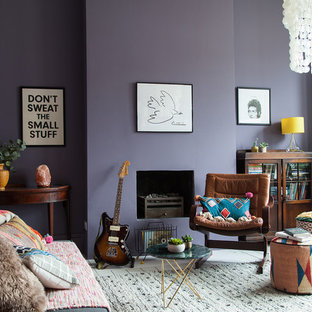 This is an example of a large bohemian study in London with purple walls, painted wood flooring, a standard fireplace, a plastered fireplace surround, a freestanding desk and white floors.