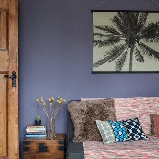 Design ideas for a large bohemian study in London with purple walls, painted wood flooring, a standard fireplace, a plastered fireplace surround, a freestanding desk and white floors.