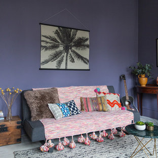 Photo of a large bohemian study in London with purple walls, painted wood flooring, a standard fireplace, a plastered fireplace surround, a freestanding desk and white floors.