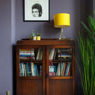 Inredning av ett eklektiskt stort hemmabibliotek, med lila väggar, målat trägolv, en standard öppen spis, en spiselkrans i gips, ett fristående skrivbord och vitt golv