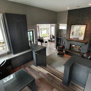 Exemple d'un grand bureau tendance avec un bureau intégré, un mur gris, un sol en bois brun, une cheminée standard et un manteau de cheminée en pierre.