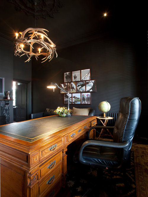 trendy freestanding desk home office photo in melbourne with black walls