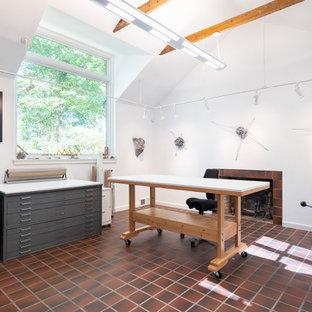 Esempio di un grande atelier moderno con pareti bianche, pavimento in terracotta, camino classico, cornice del camino piastrellata, scrivania autoportante e pavimento rosso