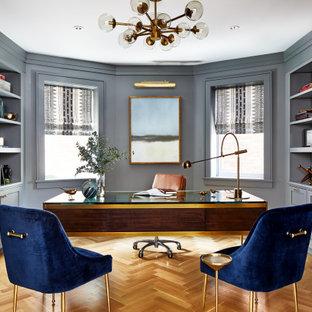 Idéer för att renovera ett stort vintage hemmabibliotek, med grå väggar, ett fristående skrivbord, brunt golv och mellanmörkt trägolv