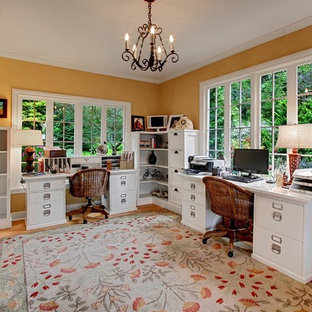 Example of a country freestanding desk medium tone wood floor home office design in Seattle with yellow walls