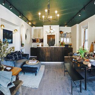 ニューヨークの中サイズのコンテンポラリースタイルのおしゃれなアトリエ・スタジオ (白い壁、クッションフロア、標準型暖炉、木材の暖炉まわり、造り付け机、グレーの床) の写真