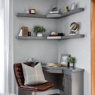 Diseño de despacho moderno, pequeño, sin chimenea, con paredes grises, suelo de madera oscura, escritorio empotrado y suelo marrón