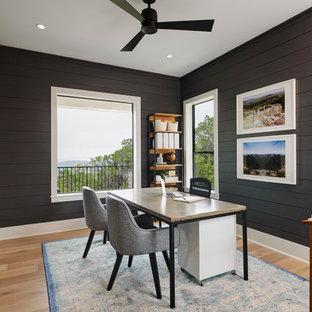 オースティンの中サイズのカントリー風おしゃれなホームオフィス・書斎 (黒い壁、淡色無垢フローリング、自立型机、茶色い床) の写真