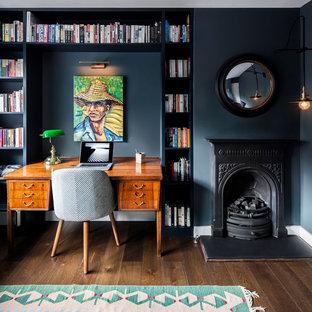 Inredning av ett eklektiskt litet arbetsrum, med svarta väggar, mörkt trägolv, en standard öppen spis, en spiselkrans i metall, brunt golv och ett bibliotek