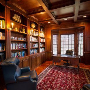 Mittelgroßes Klassisches Lesezimmer ohne Kamin mit braunem Holzboden, freistehendem Schreibtisch und brauner Wandfarbe in Raleigh