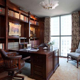 Klassisches Arbeitszimmer mit brauner Wandfarbe, dunklem Holzboden, Einbau-Schreibtisch, braunem Boden, Wandpaneelen und Holzwänden in Austin