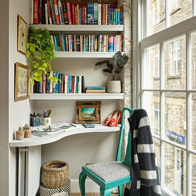 Small trendy built-in desk medium tone wood floor and brown floor home office library photo in London with gray walls